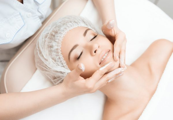 The doctor is doing a face massage for the girl. The doctor applies a special cream to the skin. The girl came to the procedure of laser hair removal. They are in the modern beauty salon.